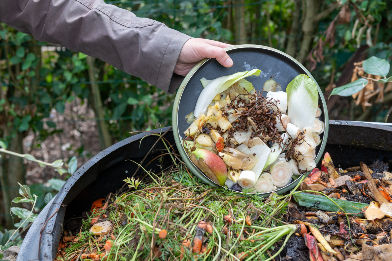 Woman throwing compost with kitchen waste