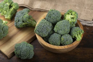 Fresh broccoli in bowl on wooden table
